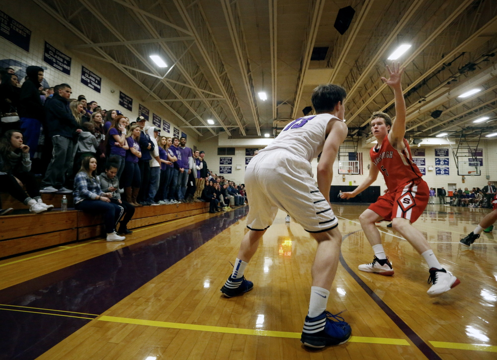 "Ian Corey of Scarborough High defends against Max Chabot of Deering High as he sets up near the 3-point line during a game at Deering. The 3-point arc is 19 feet, 9 inches from the basket. In Yarmouth, Coach Adam Smith says, ""All of our starting five have a green light to shoot the 3-pointer."""
