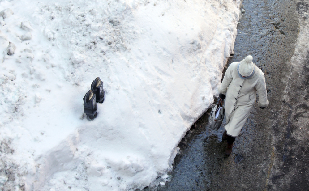 Parking meters are mostly buried in a mound of snow Friday along a street in downtown Boston. Another winter storm that could bring an additional foot or more of snow to some areas is forecast for the region beginning Saturday evening.