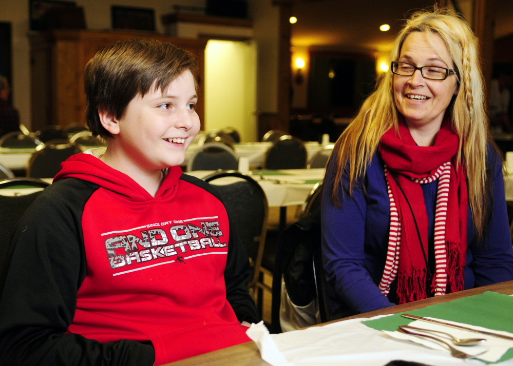 Malachi Walo and his mother, Michelle Hartman, share a laugh Thursday during an interview before an awards presentation honoring Walo's efforts to save his siblings during a January fire.