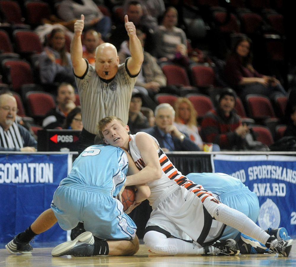Winslow's Colby Robertson, 1, battles for the loose ball with Oceanside's Nate Raye in the first half of Saturday's Eastern Class B boys' basketball quarterfinal at Bangor. Winslow won, 46-40.