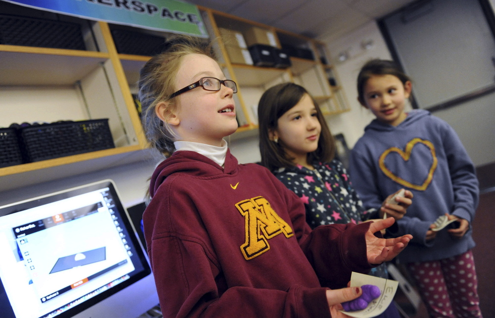"""Second-graders Ellie Englund, University of Minnesota sweatshirt, Filippa Keszti, center, and Lucy Carpenter talk in the """"maker space"""" of the new learning commons of the International School."""