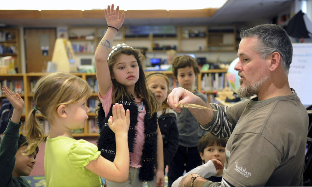 Audubon Center Education Specialist James Flynn engages with Isabel Schlaack, left, and Isabella Degani, center, in the new  learning commons of the International School at Dundee in Greenwich, Conn. But books remain a constant, with monthly circulation up 20 percent.