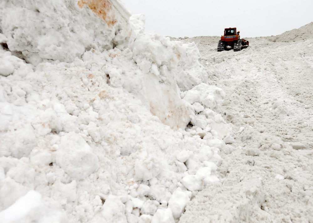 """A bulldozer works on a giant pile of snow at a """"snow farm"""" in Boston on Saturday. Crews from around the region worked urgently to remove snow Saturday as another storm bore down on the Northeast."""