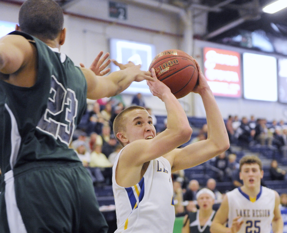 Brandon Palmer, while guarded by Deonte Ring of Spruce Mountain, looks to get off a shot for Lake Region, which will take on top-ranked Yarmouth in the quarterfinals at 9 p.m. Thursday at the Cross Insurance Arena.