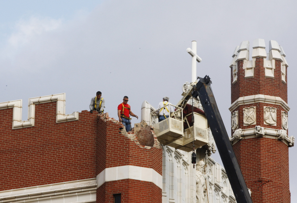 Maintenance workers inspect the damage to one of the spires on Benedictine Hall at St. Gregory's University in Shawnee, Okla., after two earthquakes hit the area in less than 24 hours.  New federal research says small earthquakes shaking Oklahoma and southern Kansas daily are dramatically increasing the chance of bigger and dangerous quakes, new federal research indicates.