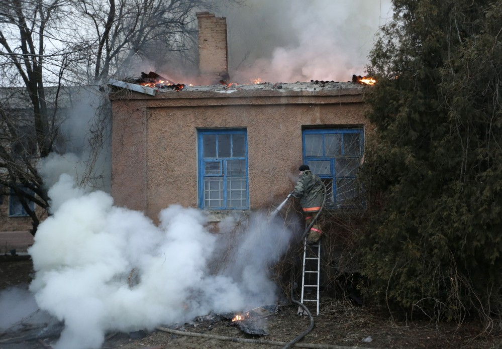 A firefighter tries to extinguish a building fire after shelling Saturday between Russian-backed separatists and Ukrainian troops in Artemivsk, Ukraine.