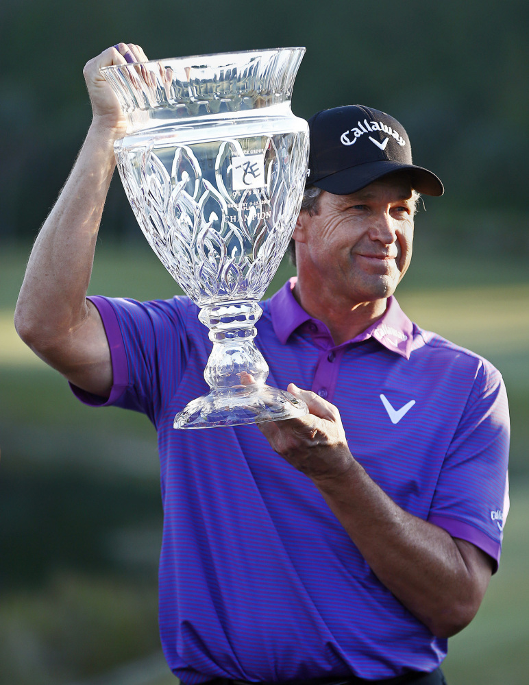 Lee Janzen holds up the first-place trophy after beating Bart Bryant on a playoff hole in the Champions Tour's ACE Group Classic at TwinEagles Golf Club on Sunday in Naples, Fla.