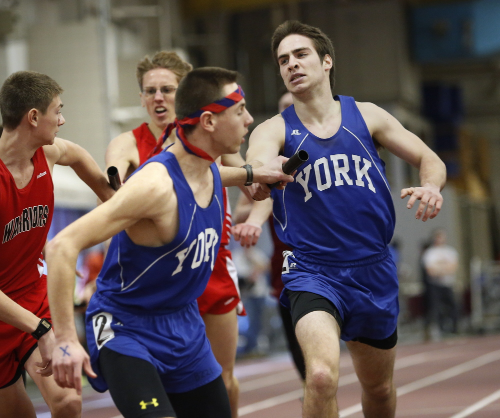 Schaeffer Rees of York hands the baton to teammate Nate Bald after the first leg of the 4x800-meter relay Monday at the Class B indoor track and field championships in Lewiston. York won the overall team championship for the third time in four years.