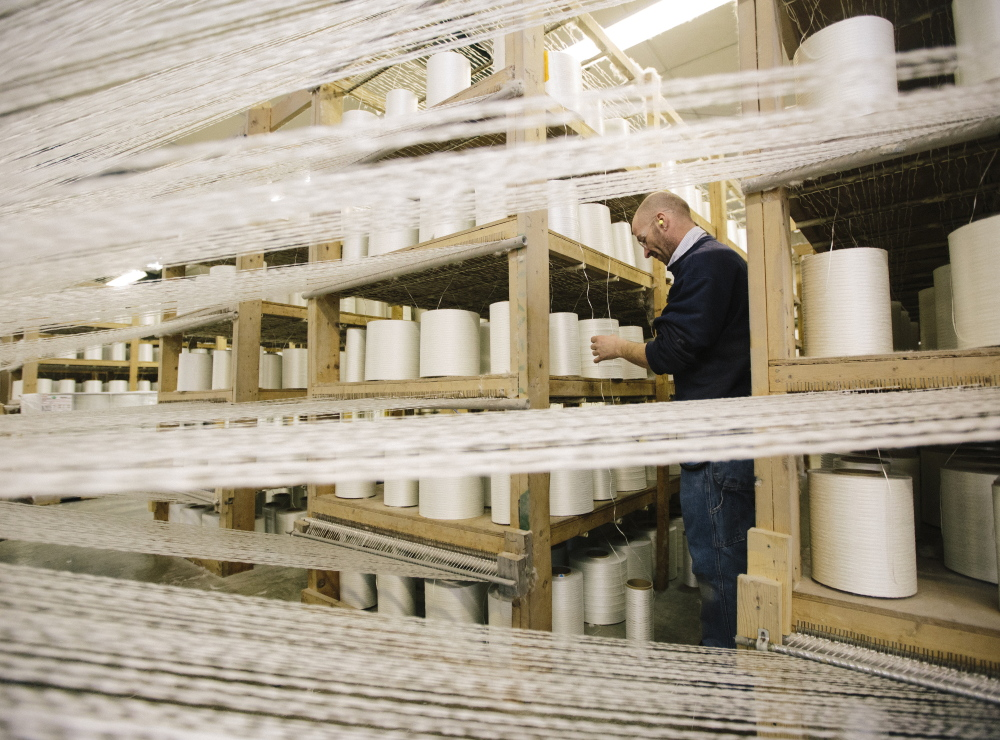 """Kirk Hall checks on the fiberglass """"yarn packages"""" feeding into an industrial loom making heat-resistant fabric at Auburn Manufacturing in Mechanic Falls."""