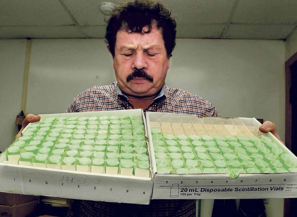 Northeast Lab Services owner Rodney Mears holds two trays of water samples to be tested for radon at the Winslow facility in this 2014 file photo. The company saw a spike in business following a new state law that requires landlords to test for radon.