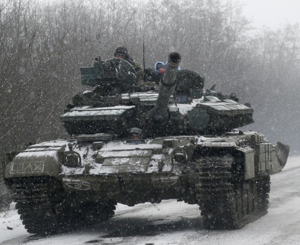 A Ukrainian armored vehicle drives on the road between the towns of Debaltseve and Artemivsk, Ukraine, Monday, Feb. 16, 2015. The Ukrainian government and Russia-backed rebels accused each other Monday of violating a cease-fire in eastern Ukraine, a day before the parties are due to start withdrawing heavy weaponry under a recently brokered deal. The cease-fire, which went into effect on Sunday, had raised cautious hopes for an end to the 10-month-old conflict, which has already claimed more than 5,300 lives. (AP Photo/Petr David Josek)