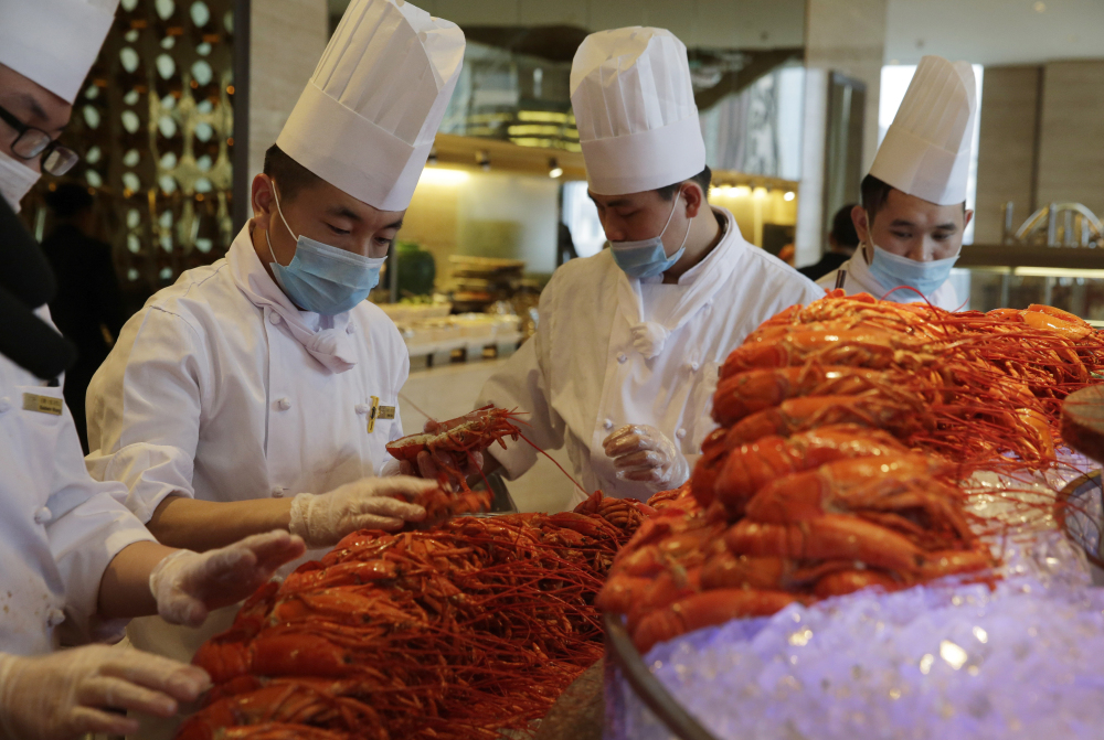 In this Feb. 9, 2015, photo, Chinese chefs prepare Boston lobsters at the Auspicious Garden restaurant in Pangu Seven Star Hotel in Beijing.