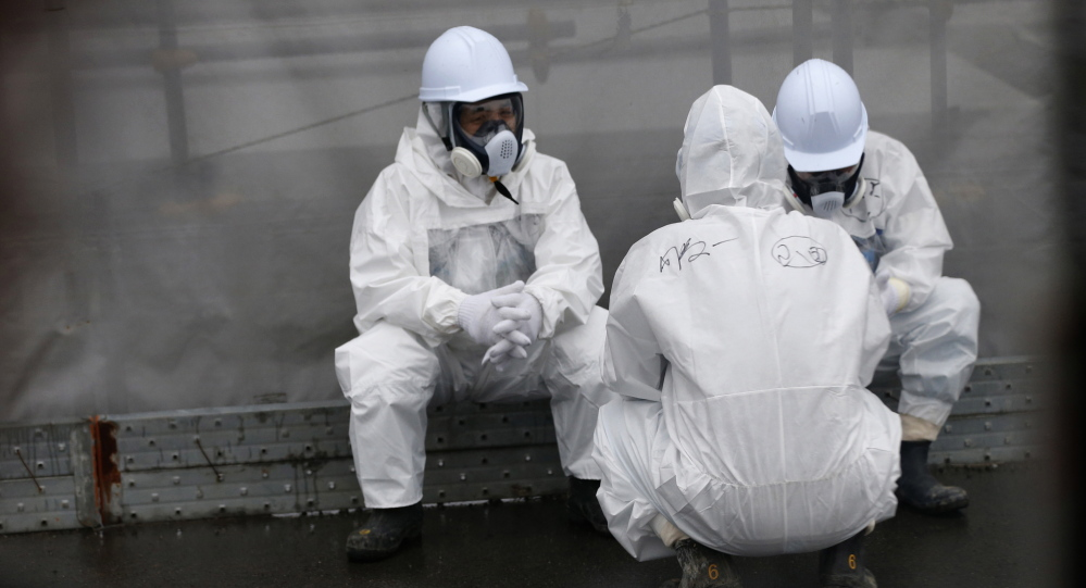 Workers wearing radiation protective gear rest near TEPCO's tsunami-crippled Fukushima Daiichi nuclear power plant.