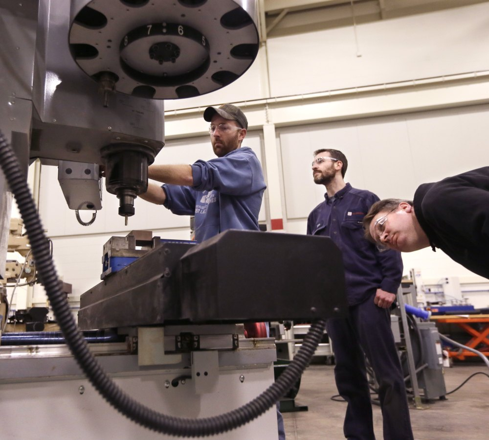 "At Lansing Community College, Brad Bancroft, left, operates a mill as others watch during a precision machining class. Gov. Rick Snyder wants to re-establish vocational and technical schooling as an ""honorable, equally important"" career track."
