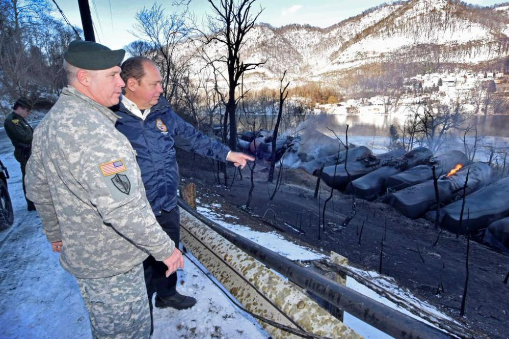 In this photo provided by the Office of the Governor of West Virginia, Gov. Earl Ray Tomblin, second from left, and Gen. James Hoyer stand near derailed train cars near Mount Carbon, W.Va., Tuesday.