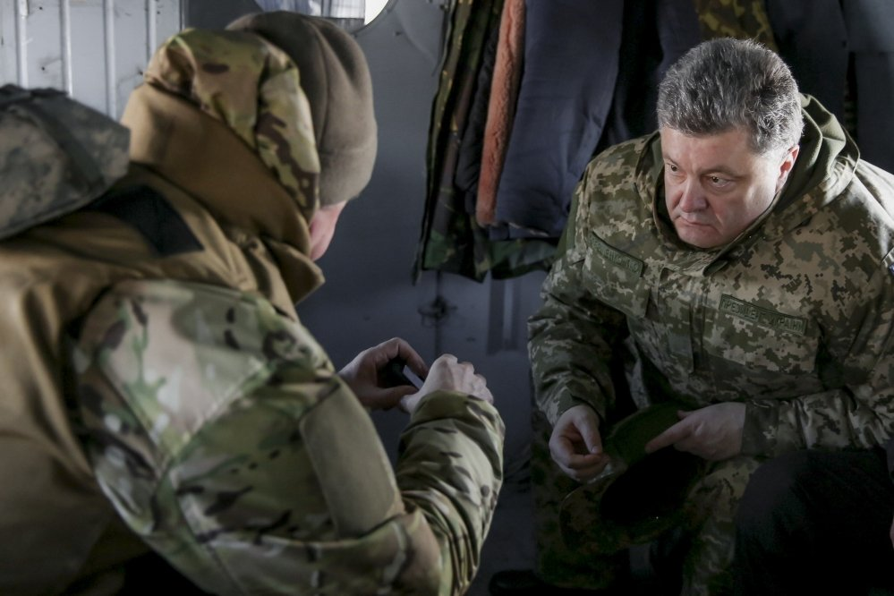 Ukrainian President Petro Poroshenko, right, speaks with a Ukrainian soldier in Artemivsk, Ukraine, Wednesday. He has called for help from an international peacekeeping mission.