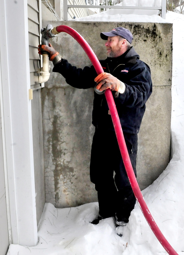 Kevin Keniston of Fabion Oil fills a tank with No. 2 heating oil Tuesday at a residence in Waterville.