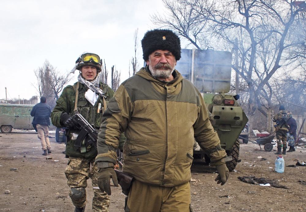 Cossack commander Nikolai Kozitsyn, a Russian national, walks through an area of the contested Ukrainian town of Debaltseve after a rebel victory there Thursday.