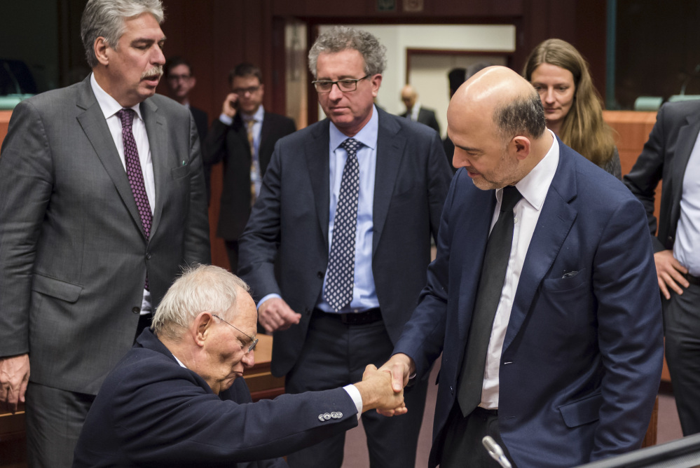 European Union Commissioner for Monetary Affairs Pierre Moscovici, right, shakes hands with German Finance Minister Wolfgang Schaeuble during a roundtable meeting of eurogroup finance ministers in Brussels on Friday.