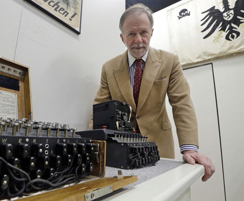 Kenneth Rendell poses Wednesday with Nazi Enigma encryption machines at his World War II Museum in Natick, Mass. The museum has more than any entity but the NSA.