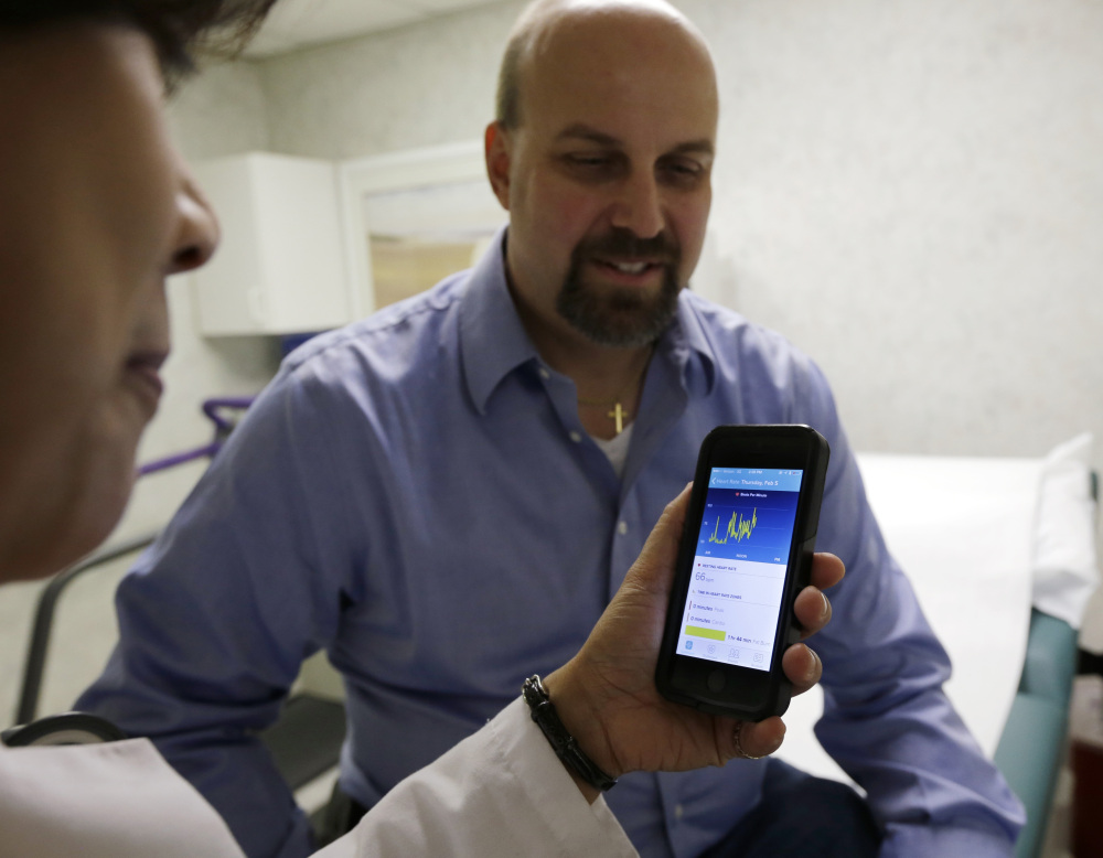 Hackensack University Medical Center cardiologist Dr. Sarah Timmapuri, consults data on a smartphone synchronized to a new Fitbit Surge worn by patient Gary Wilhelm, 51, during an examination in Hackensack, N.J., on Feb. 5.