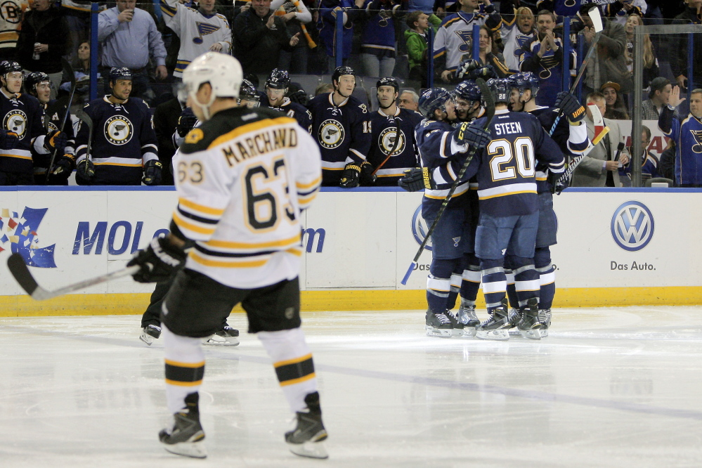 The Bruins' Brad Marchand skates off the ice as St. Louis Blues teammates congratulate Petteri Lindbohm after his goal in the second period of the Blues' win Friday night in St. Louis.