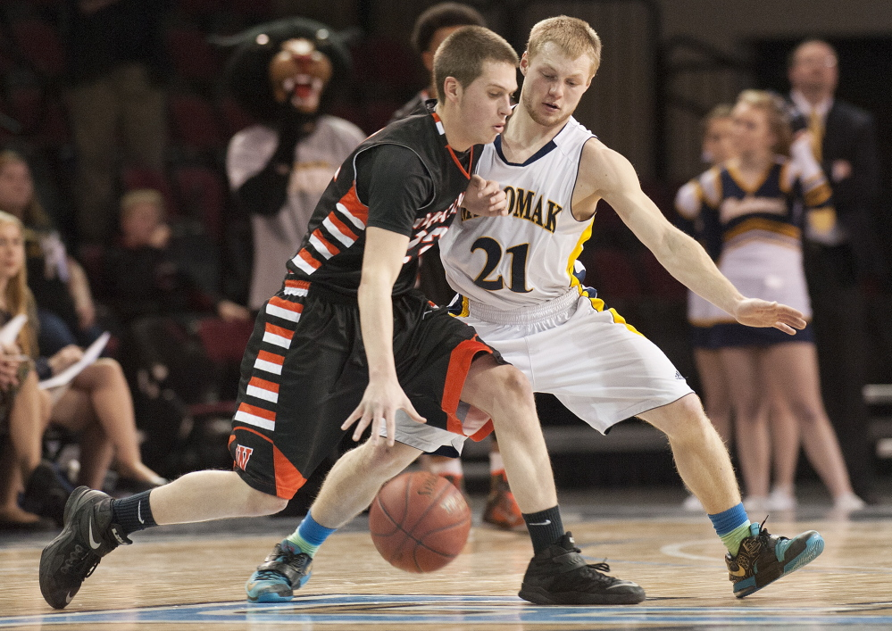 Winslow's Josh Kervin is closely guarded by Zach Starr of Medomak Valley during the Eastern Class B boys' basketball final Saturday at the Cross Insurance Center in Bangor. Medomak Valley won, 51-48.