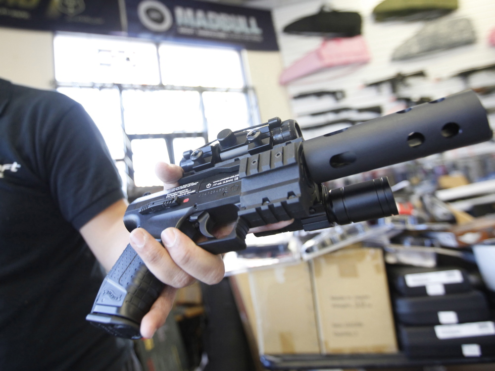 Jordan Baylon, 22, holds a realistic-looking air gun. For him and many others in the world of airsoft fighting, the appeal of the weapons lies in their realism. (Bob Chamberlin/