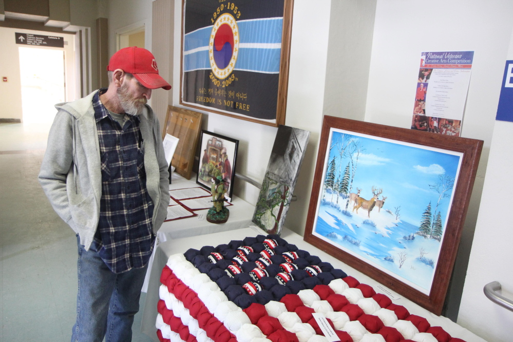 Rodger Sweeney of Exeter, looks at artwork Saturday at the 2015 Maine Veterans Creative Arts Festival.