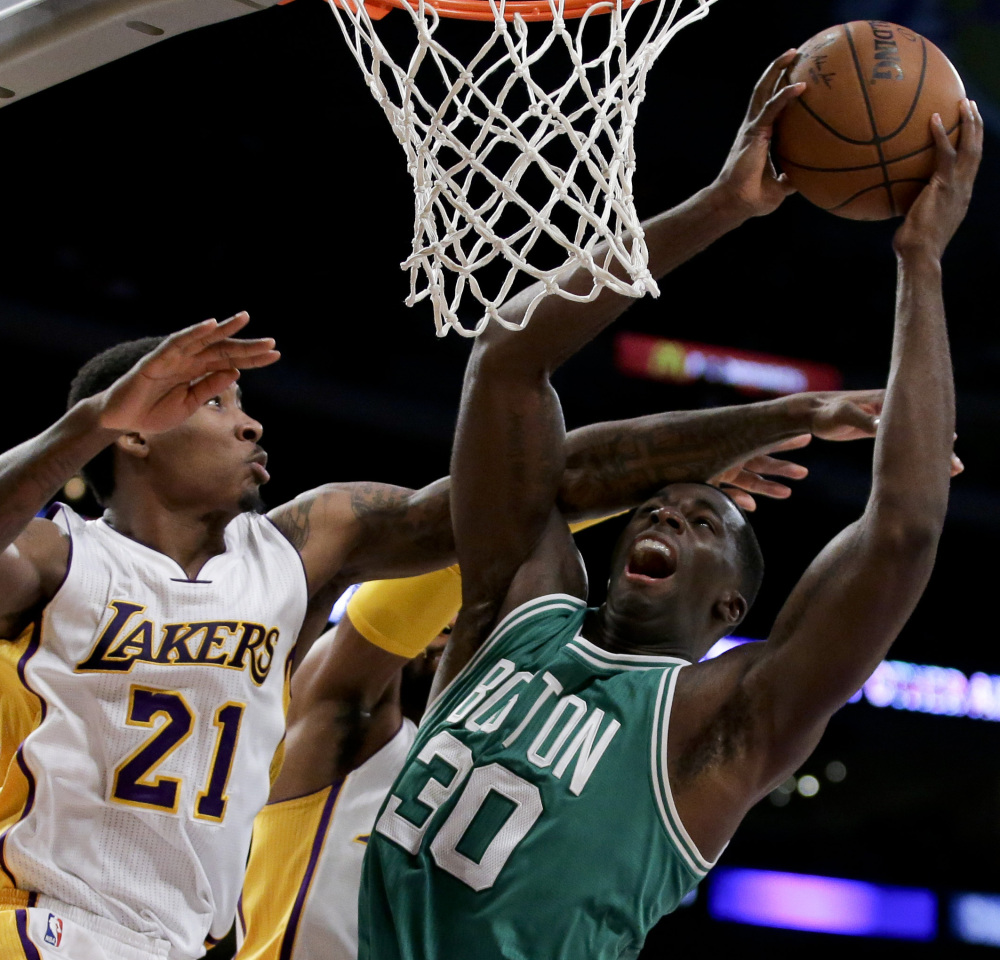 Celtics center Brandon Bass, right, takes a shot while being defended by Lakers forward Ed Davis during the first half of their game Sunday in Los Angeles. The Lakers won, 118-111 in overtime.