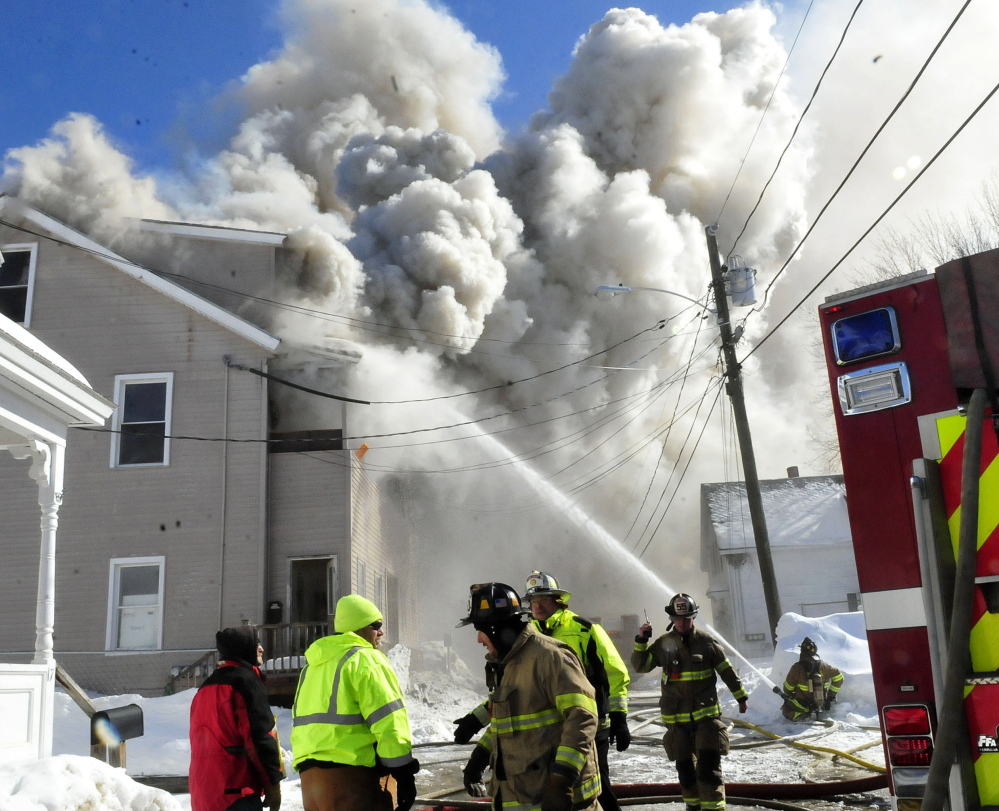Wind-blown smoke billows from an apartment building on Paris Street in Waterville that was destroyed by fire Monday.