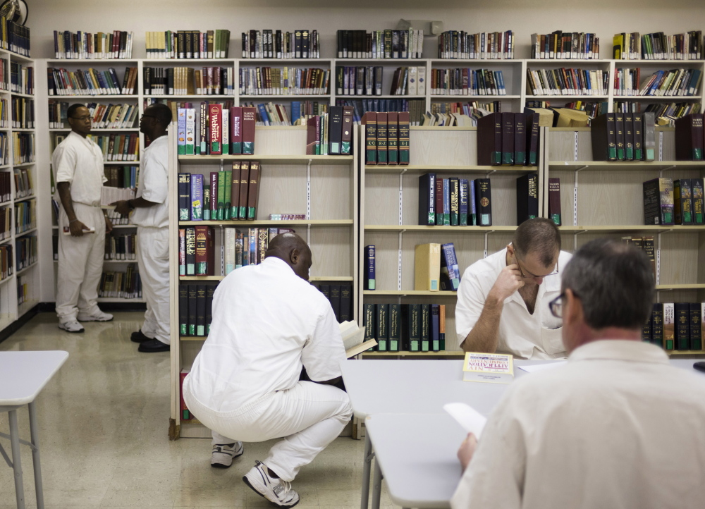 Inmates use the library at the men's prison in Rosharon, Texas. Several states rely on surveys to assess the risk of repeat offenses.