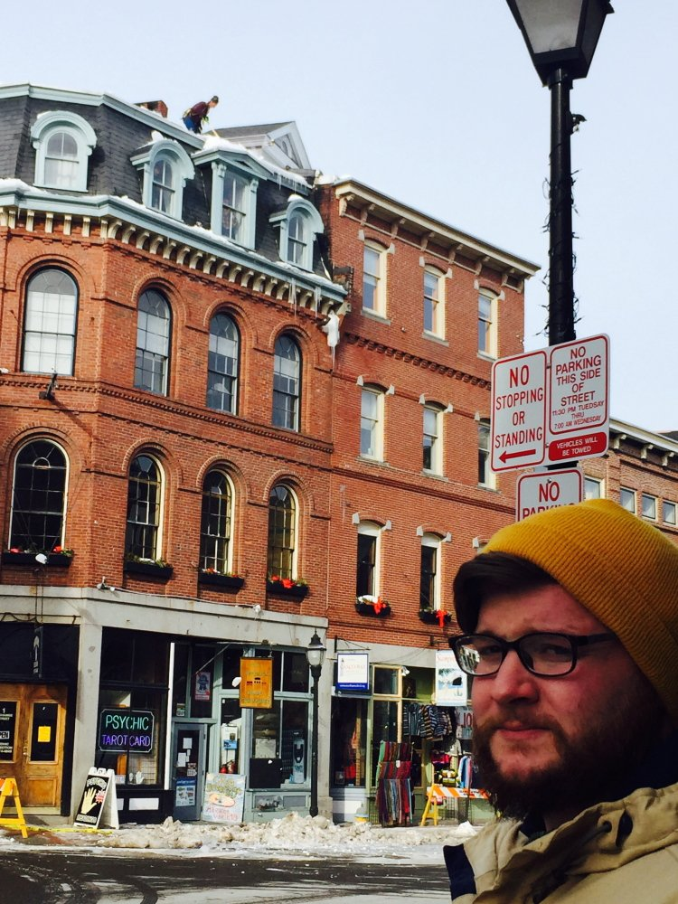 Adam Sousa stands in front of the building at the corner of Exchange and Fore streets, where large pieces of ice fell on his car Sunday. He has since received broad support from the community to get back on the road.