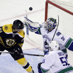 Vancouver Canucks goalie Eddie Lack keeps an eye on the rebounding puck as Bruins left wing Loui Eriksson watches along with Canucks defenseman Alex Biega during the third period of Tuesday night's game in Boston. The Bruins lost, and now have just one win in their last nine games.