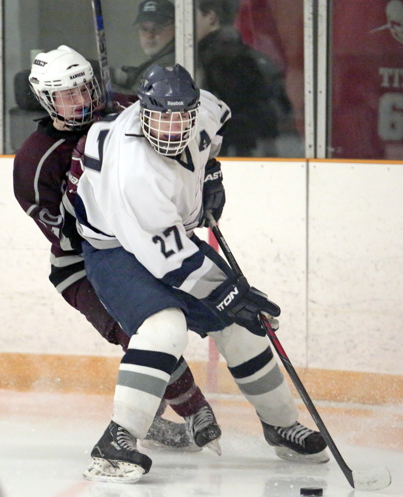 Yarmouth's Walter Conrad fends off Greely's Colby Williams in a Western Class B quarterfinal Tuesday night at the Travis Roy Arena in Yarmouth. Conrad had a goal and an assists in Yarmouth's 4-2.
