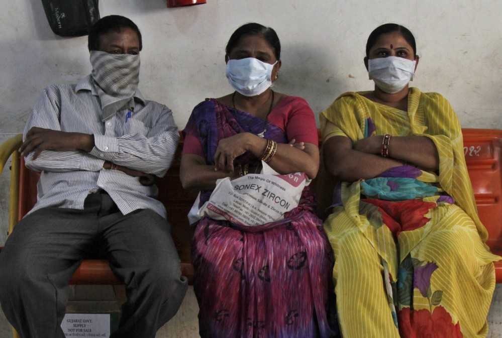 Relatives of swine flu patients sit outside an isolation ward at the Civil Hospital in Ahmadabad, India, on Wednesday.