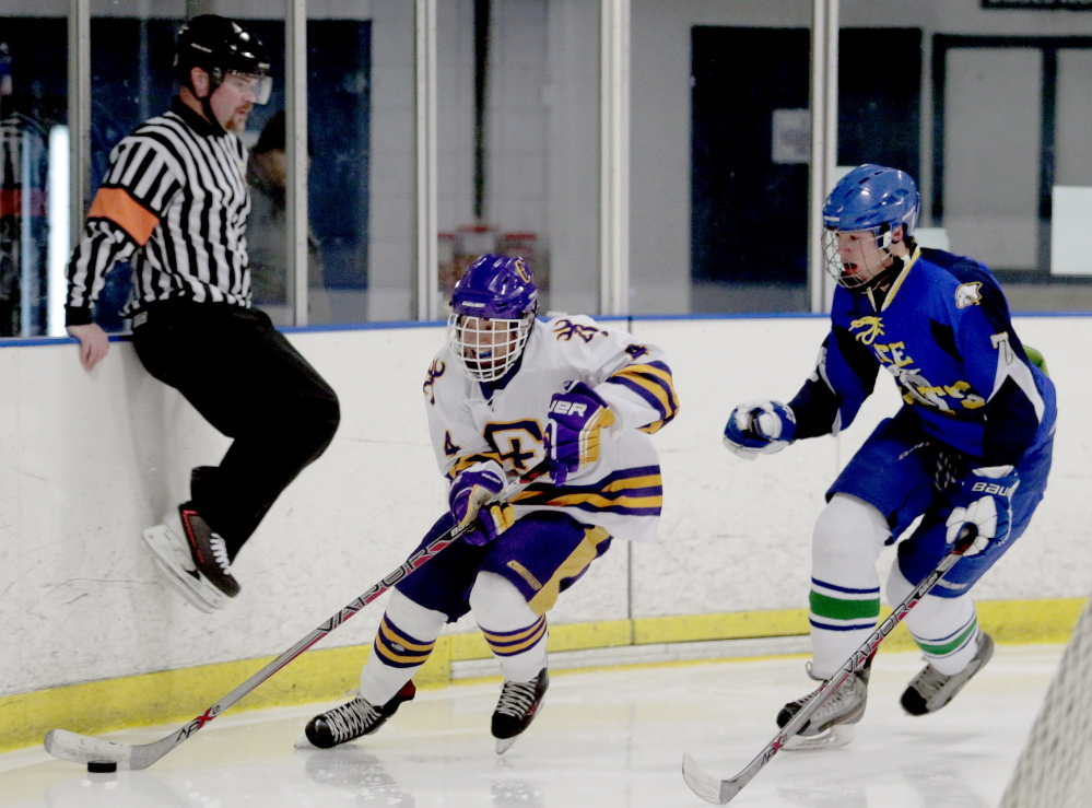 Jesse Cyr-Brophy of Cheverus skates with the puck while being chased by Gabe Sappington of Lake Region/Fryeburg/Oxford Hills in Wednesday's Western Class A quarterfinal won by the Stags 12-1 at Troubh Ice Arena in Portland.