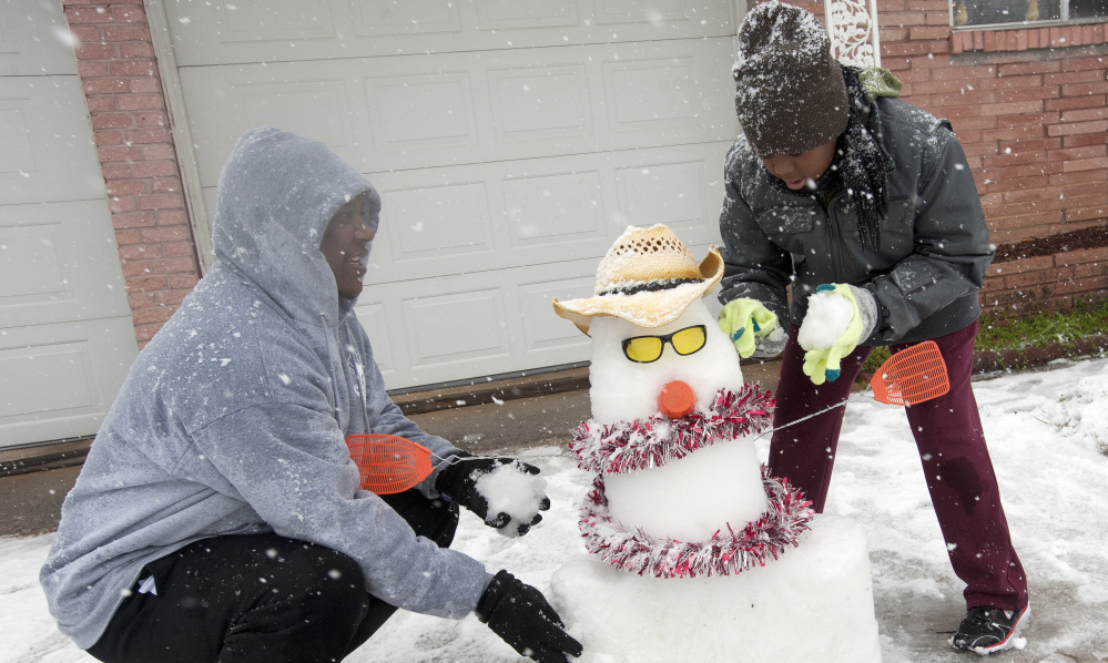 Kenneth Scott, left, and his son Kanya build a snowman Wednesday in Tyler, Texas. Six to 8 inches of snow or more fell from north Texas to Virginia.