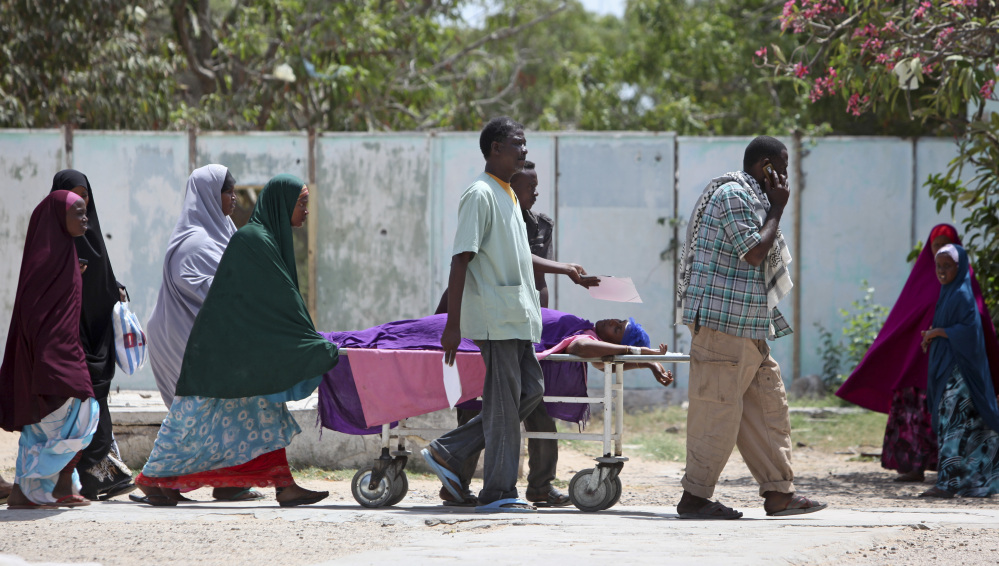 Relatives help a woman who was wounded during a mortar attack on the presidential palace, as she is moved on a stretcher to a hospital in the capital Mogadishu, Somalia Thursday, Feb. 26, 2015. A Somali police officer says that at least three mortars landed inside Somalia's heavily fortified presidential palace compound, with al-Shabab claiming responsibility for the shelling, according the group's radio station, Andulus.