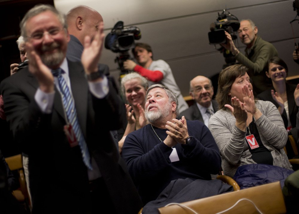 """Apple co-founder Steve Wozniak, center, and his wife Janet Hill, right, joins members of the audience in applauding at an open hearing at the Federal Communications Commission in Washington on Thursday. The FCC voted in favor of rules aimed at enforcing what's called """"net neutrality."""""""