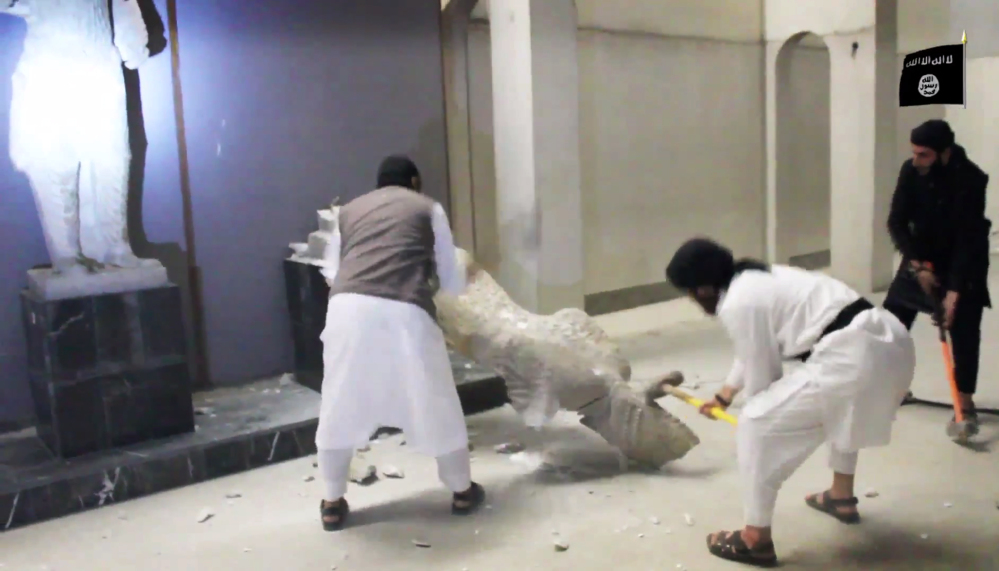 Militants take sledgehammers to an ancient artifact in the Ninevah Museum in Mosul, Iraq. The militants are also believed to have sold ancient artifacts on the black market to finance their bloody campaign.