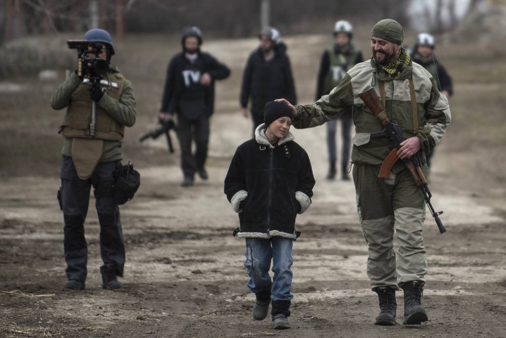 A Ukrainian serviceman speaks with a schoolboy in the village of Chermalyk, eastern Ukraine, on Thursday. In a long-awaited development, Ukrainian forces and separatist fighters both announced Thursday they are moving heavy weapons from the front line in eastern Ukraine. The Associated Press