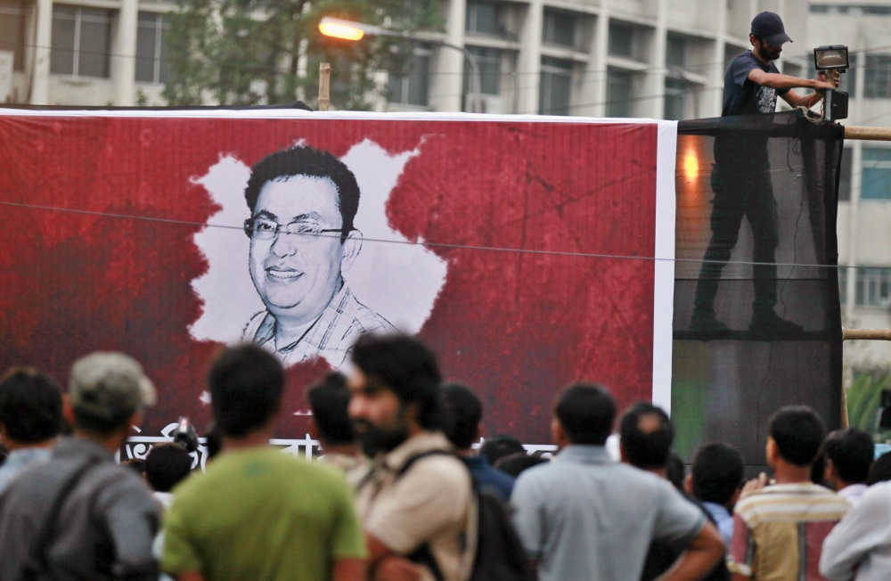 A Bangladeshi activist sets up a light on a poster displaying a portrait of Avijit Roy as others gather during a protest against the Roy in Dhaka, Bangladesh, on Friday.