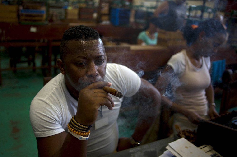 Quality control employee Manuel Lamoth, 30, smokes a cigar at the Corona cigar factory in Havana, Cuba, Thursday. Cuban cigar makers are happy with new U.S. rules that let more Americans travel to the island and legally bring back as much as $100 worth of cigars for the first time in decades. Officials said during this week's annual cigar festival that this year alone, they expect to double sales of hand-rolled