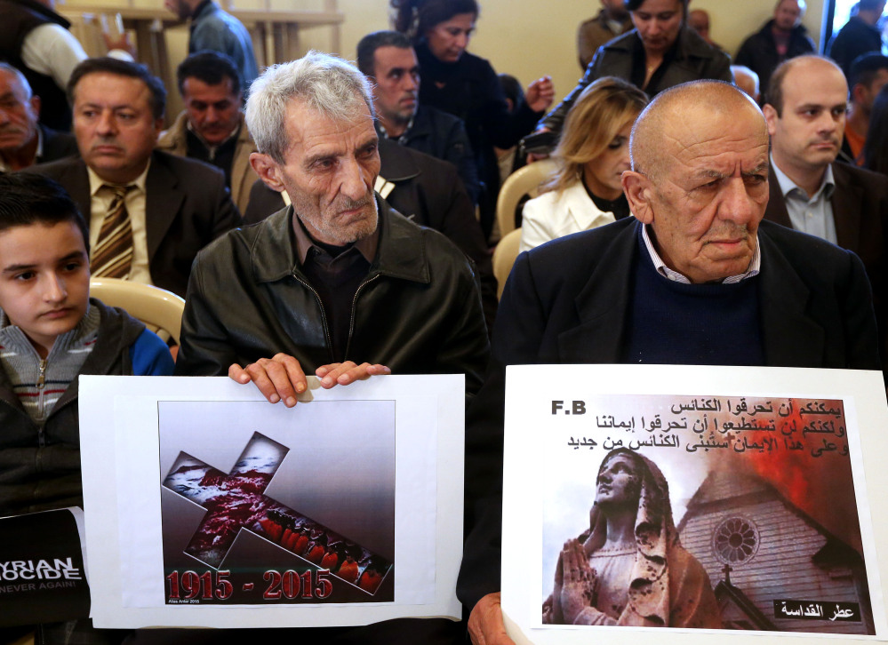 "Assyrian citizens hold placards during a sit-in in Beirut for abducted Christians in Syria and Iraq. The placard at right reads, ""You can burn the churches but you cannot burn our faiths, and in this faith we will rebuild the churches."""
