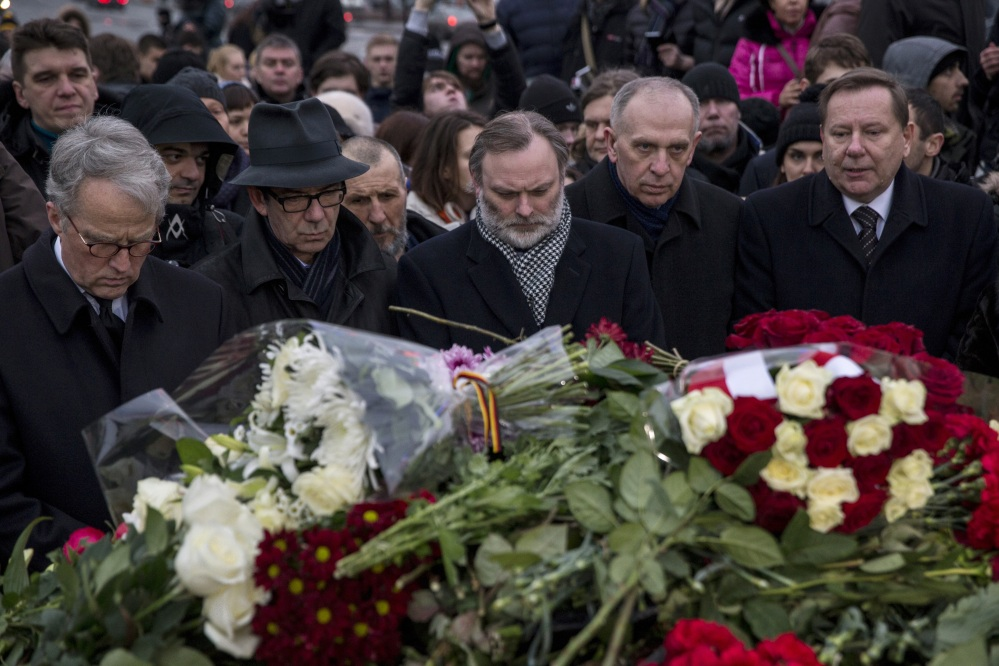 A group of EU ambassadors to Russia lay flowers at the place where Boris Nemtsov, a charismatic Russian opposition leader and sharp critic of President Vladimir Putin, was gunned down, at Red Square, with St. Basil Cathedral in the back and the Kremlin at left, in Moscow, Russia, Saturday.