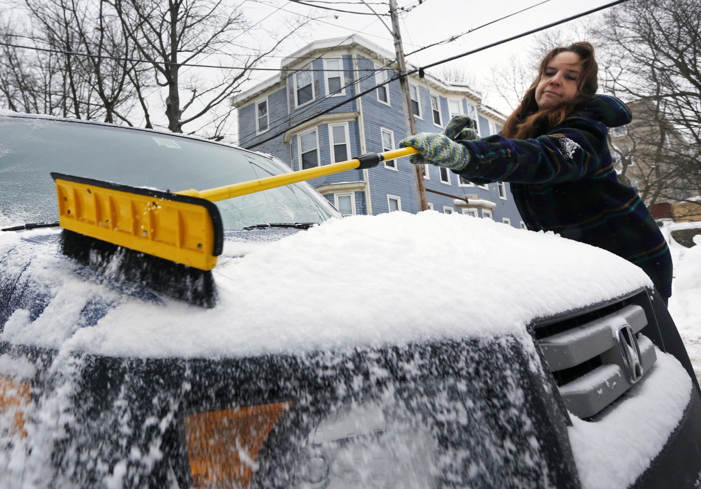 Karen Landis of Portland brushes a fresh layer of snow from her vehicle Sunday. Derek Davis/Staff Photographer