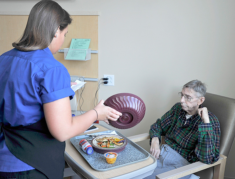 Nutrition Services Partner Megan Bean serves a stir-fry meal with locally grown carrots to Maine Medical Center patient Paul Burd of Hallowell.