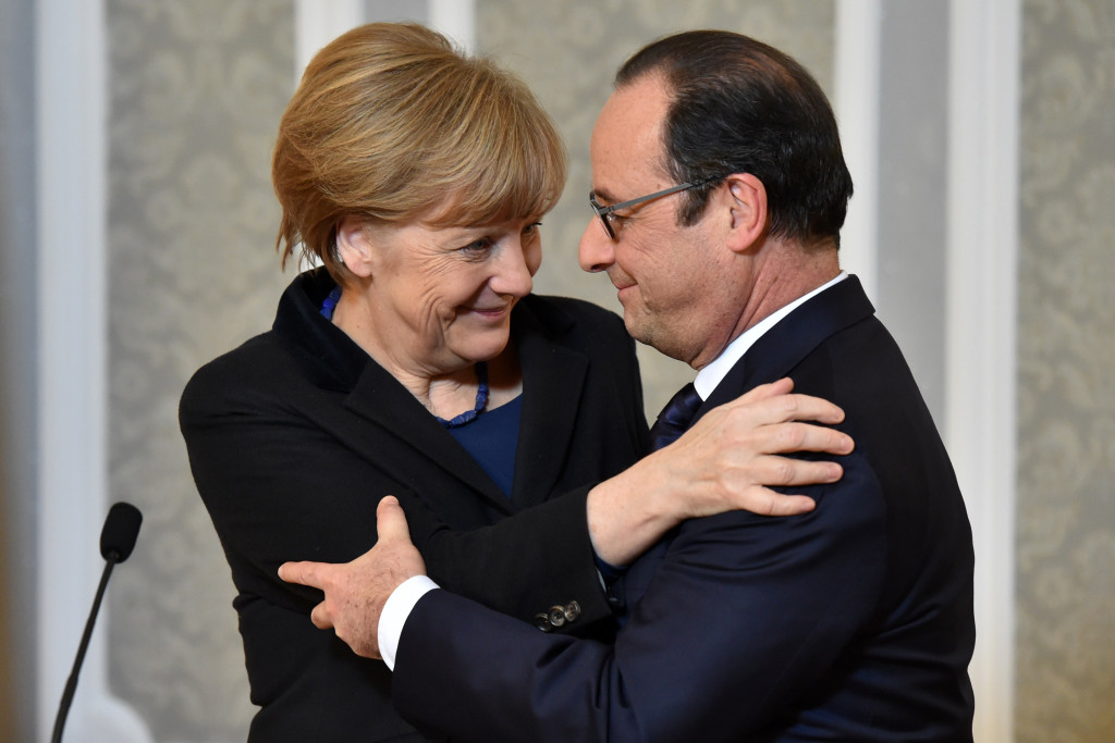 French President Francois Hollande,  and German Chancellor Angela Merkel hug after their marathon talks in Minsk, Belarus, Thursday. Hollande says he and German Chancellor Angela Merkel are committed to helping verify the cease-fire process in Ukraine, along with the Russian and Ukrainian leaders. He said  the  cease-fire deal has come as a