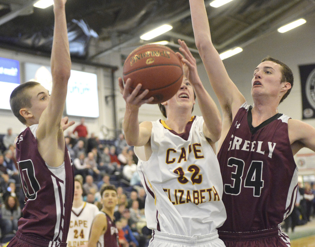 Cape's James Bottomley, 32, slips between Greely defenders Ryan Twitchell, left, and Matt McDevitt  for a layup in Saturday's Western Class B boys' basketball quarterfinal at the Portland Expo. John Ewing/Staff Photographer